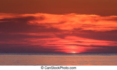 Red Sunset above Sea Sun Disk Hides behind Horizon -...