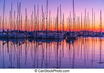 Red sunset on the harbor of sailboats