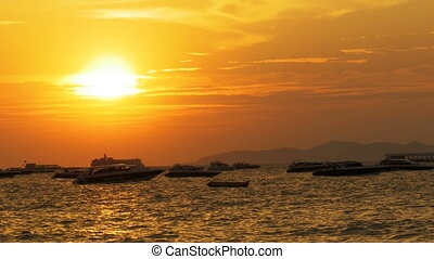 Red Sunset on the sea with silhouette boats swaying on the waves. Thailand. Pattaya