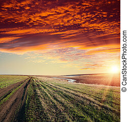 red sunset over river and rural road with dramatic sky