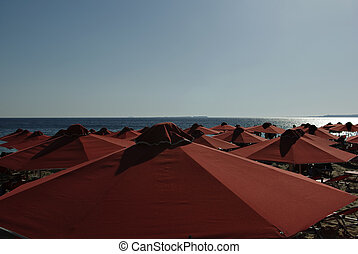 Red Sunshades - Red sunshades and sunbeds at sandy beach at ...
