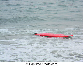 Red Surfboard Floating in Ocean