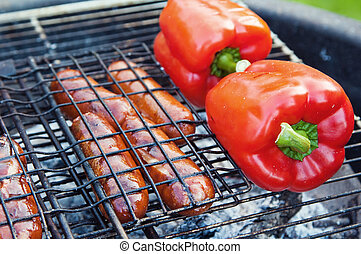 Red sweet pepper and sausages on a grill, close up