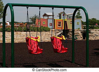 Two red swings in playground with a playhouse behind them