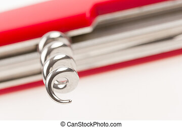 Red swiss army knife isolated, focus on corkscrew