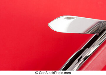 Red Swiss army knife on red background