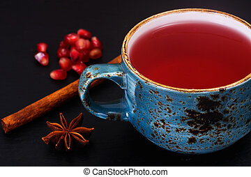 Red Tea with beautiful cup, decorated with cinnamon and pomegranate.