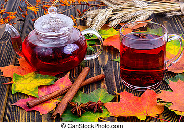 Red tea with karkade, autumn leaves on wooden table