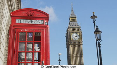 Traditional red telephone booth. Big Ben and street lights against blue sky. Famous place and tourist destination landmark in London, England, UK, Europe.