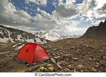 red tent in high mountains at sunset