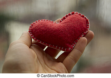 Red textile heart on the woman hand