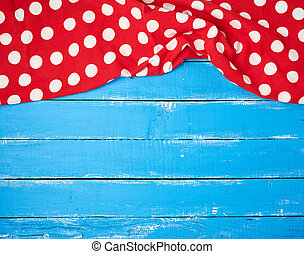 red textile towel with white circles on a blue wooden background