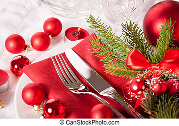 Red themed Christmas place setting with a colorful red napkin on white plates decorated with small red Xmas baubles and burning tea lights for a festive seasonal table