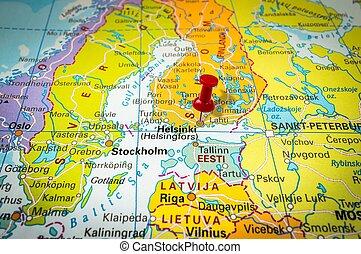 Red thumbtack in a map, pushpin pointing at Helsinki