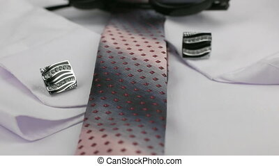 Red tie, cufflink and sunglasses on a white shirt, close-up. Dolly shot.