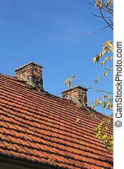 red tile roof and two chimneys