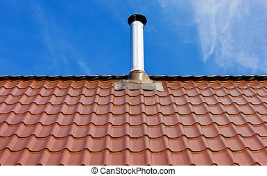 Red tile roof with a tin chimney under the sun on a blue sky...
