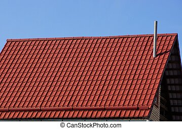 red tile roof with chimney against the blue sky