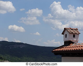 Red Tiled Roof with a Chimney against the Background of a Landscape