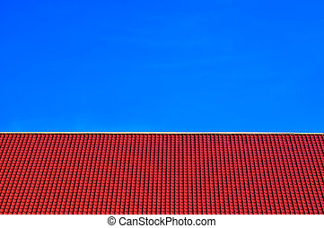 Red tiles roof on clear blue sky background