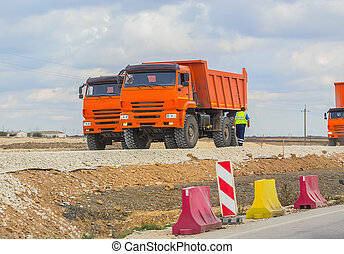 Red tippers o road under construction.