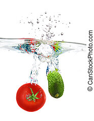 red tomato and green cucumber dropped into water isolated on white