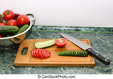 red tomato and green cucumbers slices with knife on board