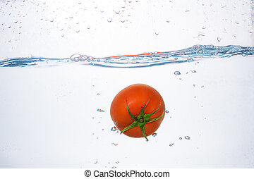 red tomato dropped into blue water on white