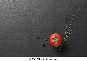 red tomato with green onion on black