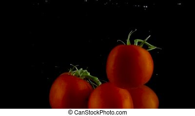 Red tomatoes fall and float in water, black background - Red...