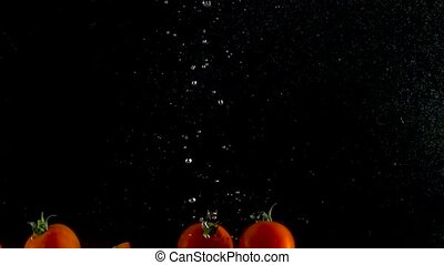 Red tomatoes fall and float in water, black background, slow motion