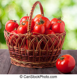red tomatoes in a wicker basket on dark wooden table