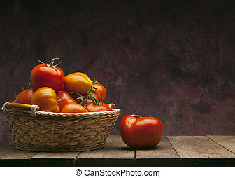 red tomatoes in basket on dark background