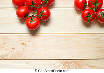 Red tomatoes on light wooden table with copy space. Top position.