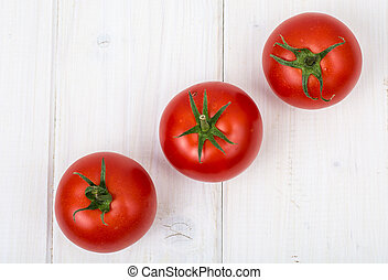 Red tomatoes on white wooden background