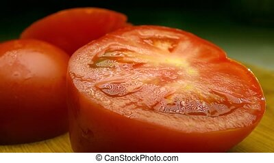 Red tomatoes on wooden cutting board being sprayed with water. Super slow motion shot