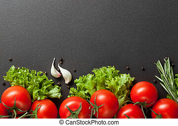 red tomatoes with green salad on black