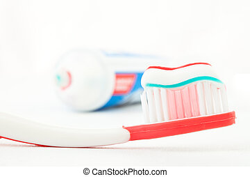 Red toothbrush with toothpaste against white background