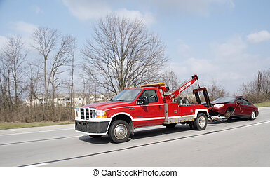 Red tow truck towing a car down a highway.