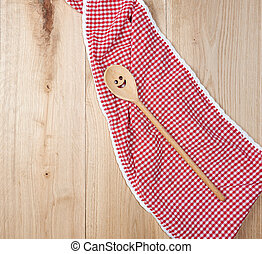 red towel and spoon on brown wooden background