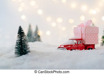 Red toy car carrying Christmas gift.