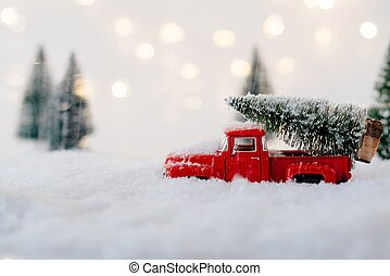 Red toy car carrying Christmas tree.