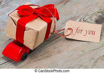 Red toy car delivering gift box for Valentine's day with tag with text: for you on wooden background