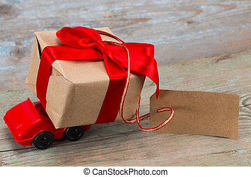Red toy car delivering gifts box with tag with empty space for a text on wooden background