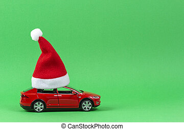 Red toy car with Christmas Santa Claus hat on light green background