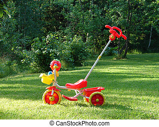 Red toy children's bicycle on green grass