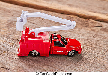 Red toy fire truck, wooden background.