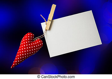 Red toy heart and blank card on black