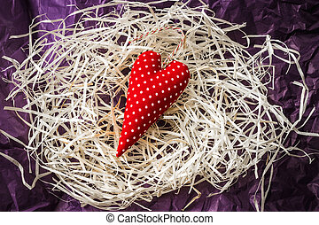 Red toy heart and blank card on straw