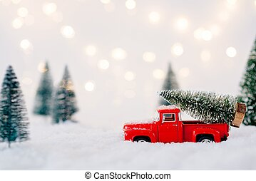 Red toy pickup car carrying Christmas tree
